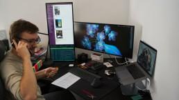 IT-Kollege im Home Office mit mehreren Bildschirmen (IT-Leiter, IT-Leiterin)